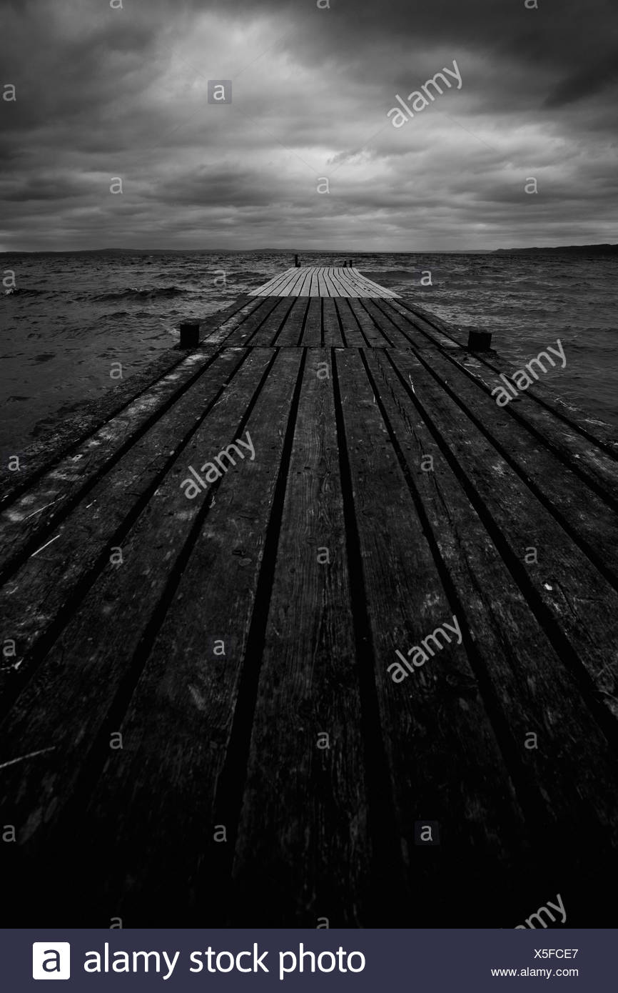 Close-up of pier with horizon over water - Stock Image