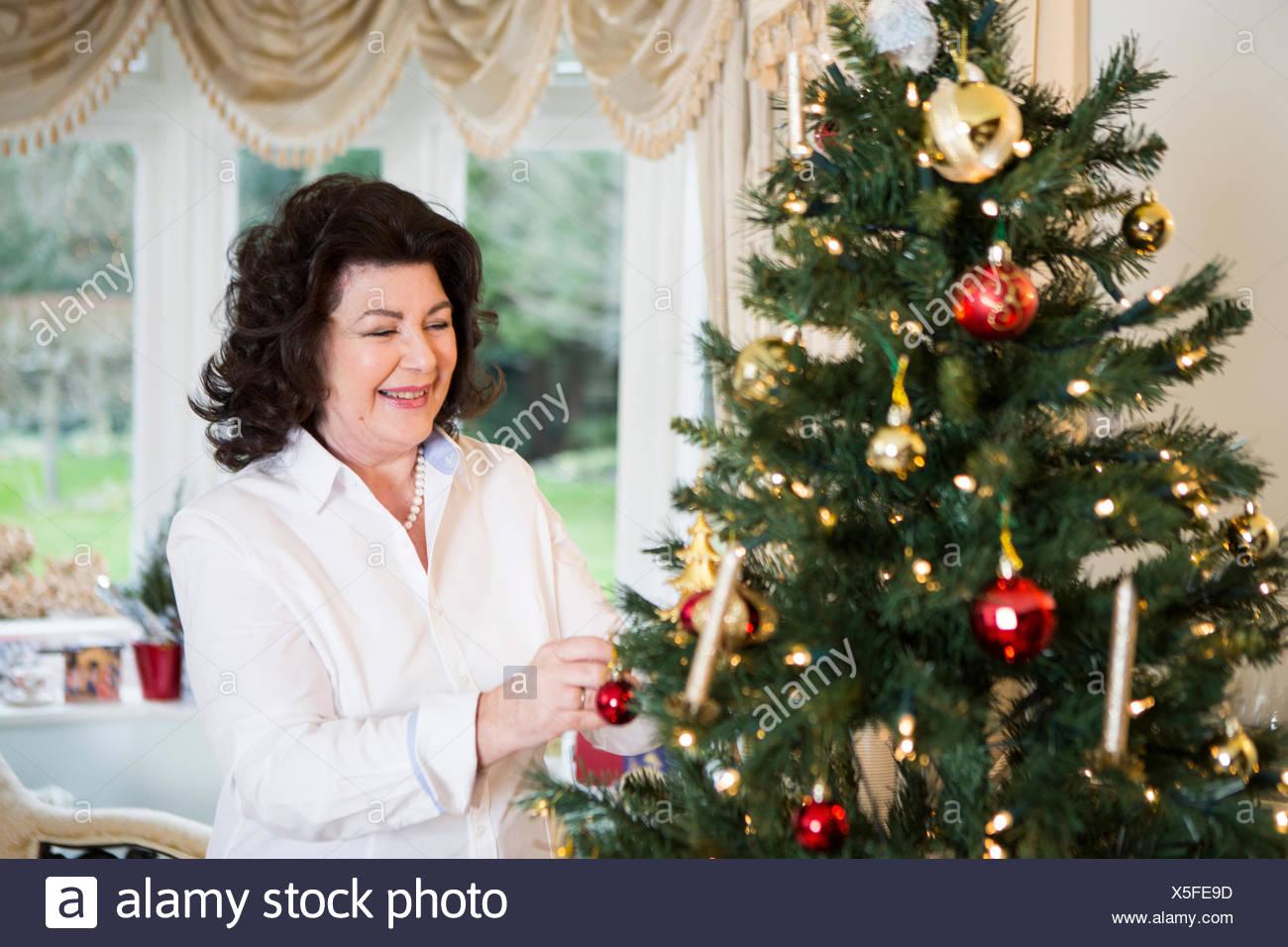 Senior woman decorating Christmas tree - Stock Image