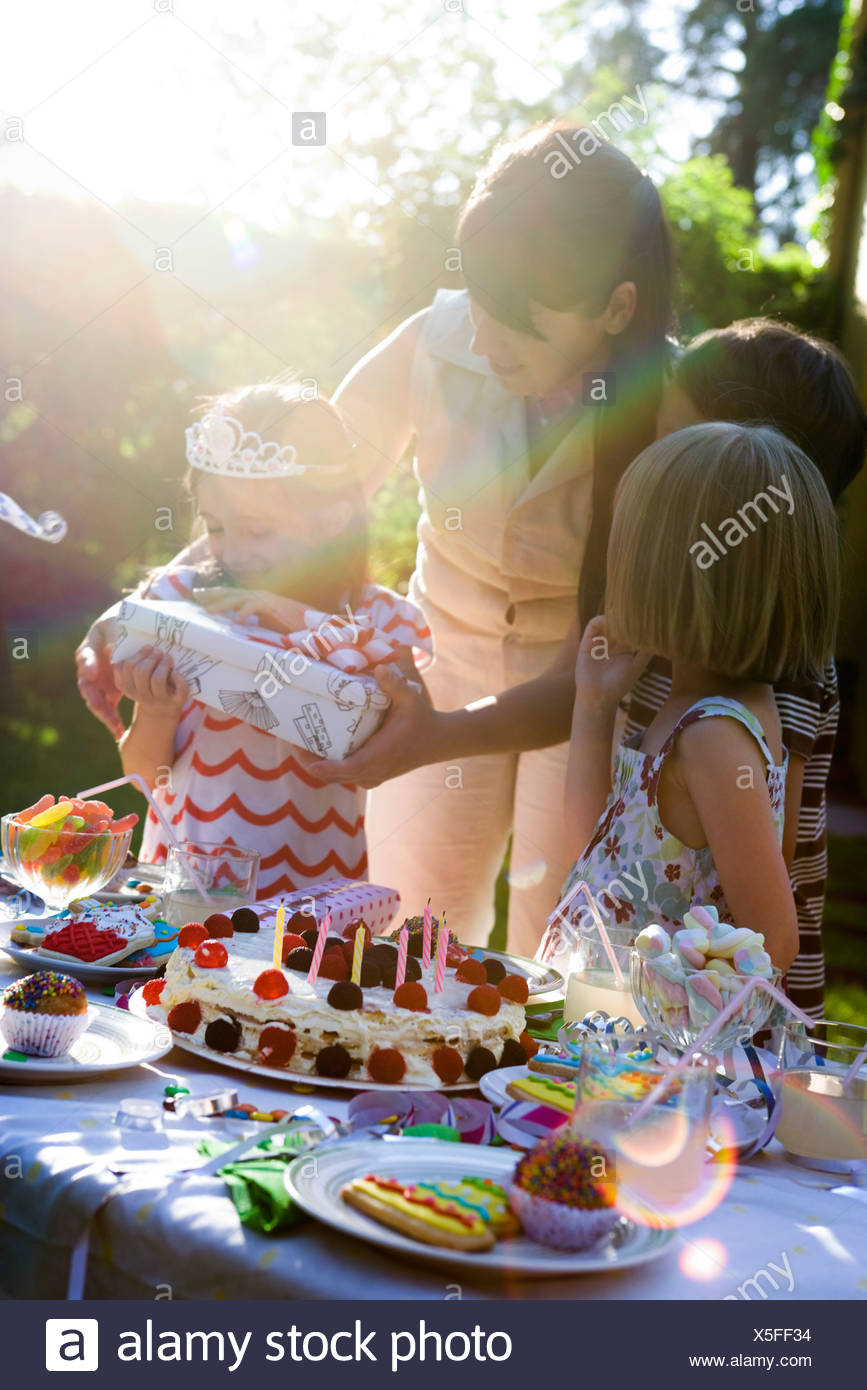 Girl opening gift at outdoor birthday party - Stock Image
