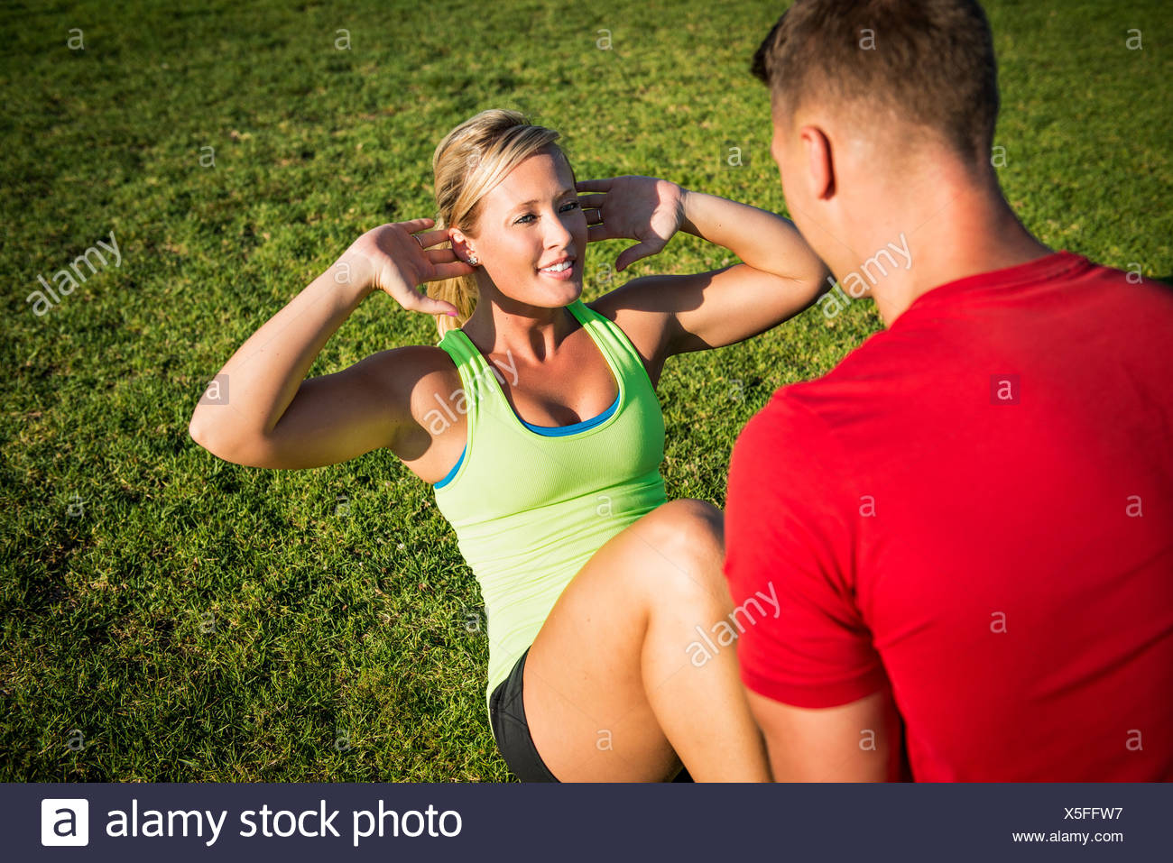 Young woman in park with trainer doing sit-ups - Stock Image