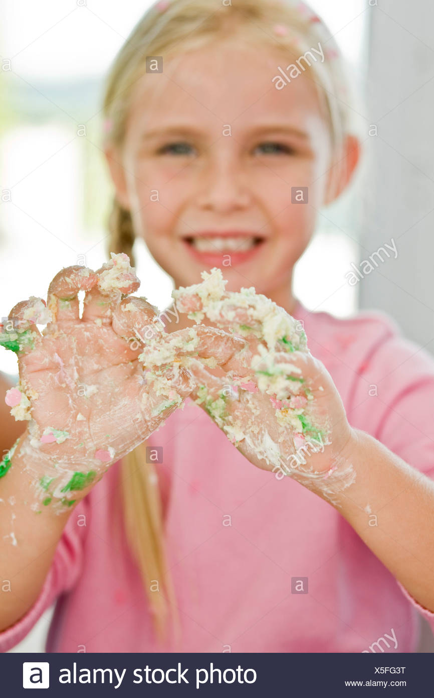 Portrait of a girl showing her messy hand covered with cake icing - Stock Image