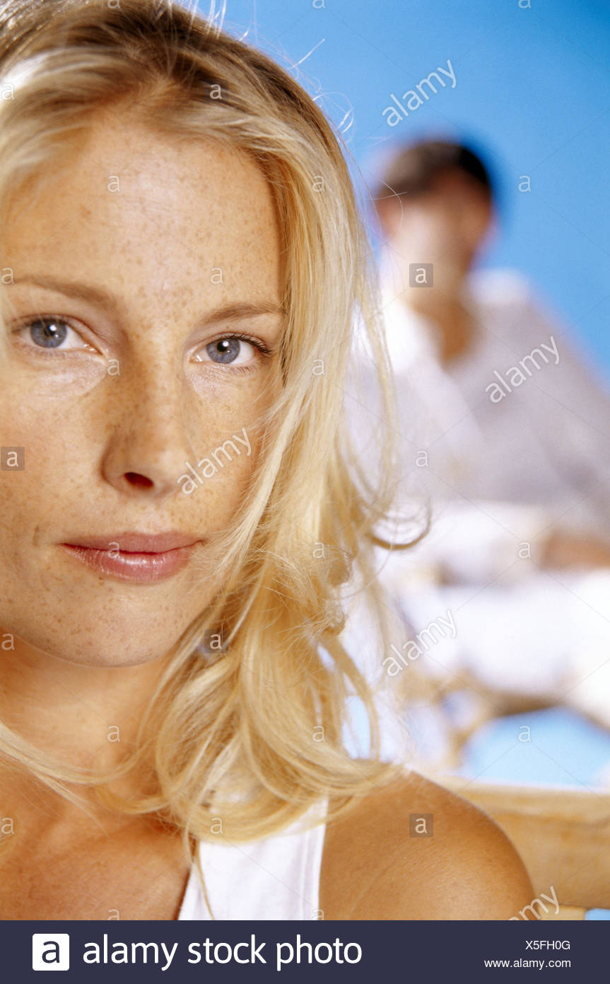 Woman, sit young, portrait, detail, background, man, blur, women's portrait, blond, long-haired, curled, seriously, sadly, partnership, respect, fight, discord, turn away, silence, conflict, problems - Stock Image