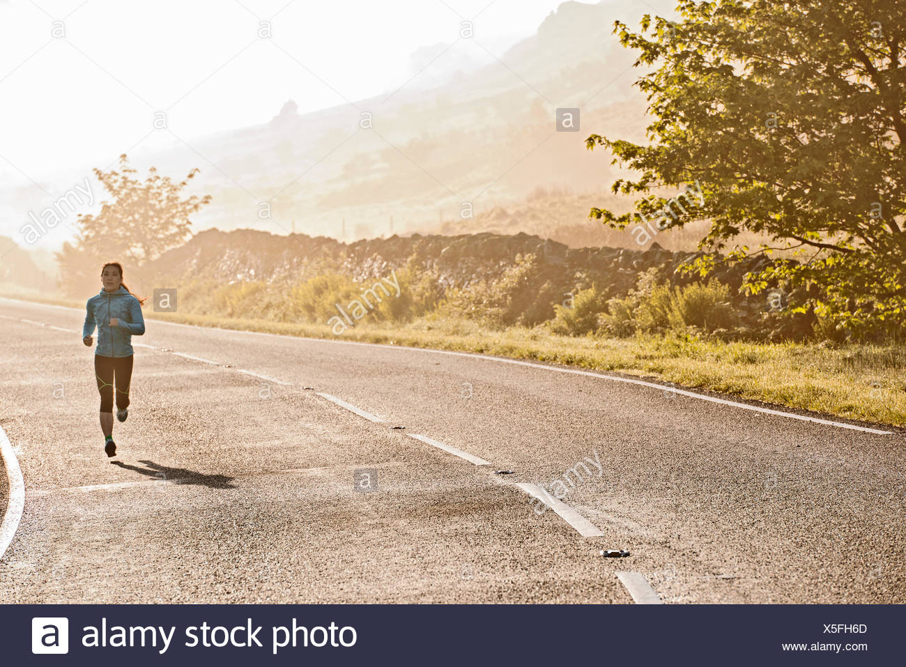 Rear view of female runner running on misty road in morning, Capel Curig, Snowdonia, North Wales, UK - Stock Image