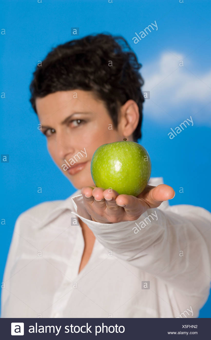 Young woman holding an apple, portrait - Stock Image