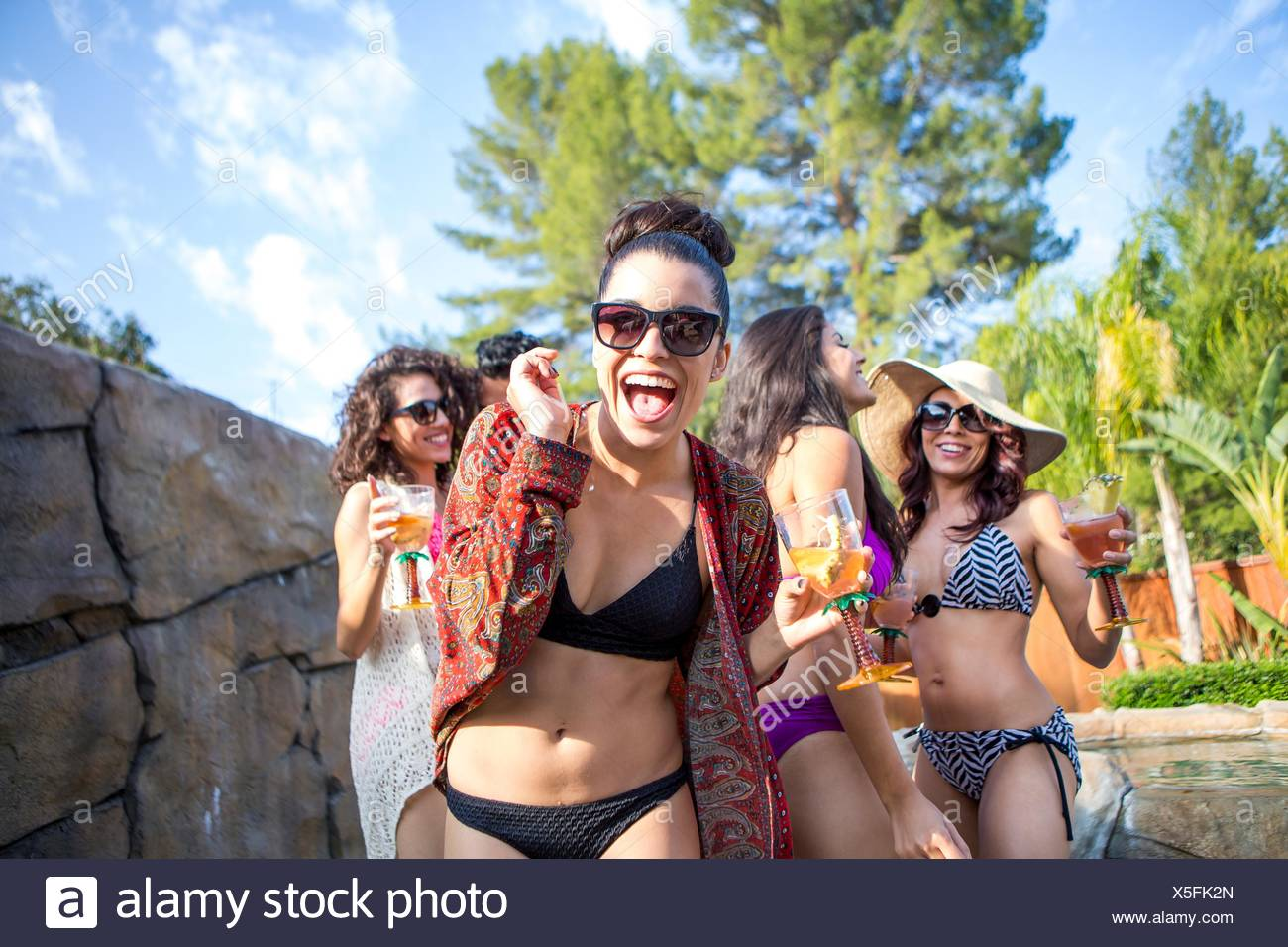 Young woman with sisters and brother drinking cocktails in garden - Stock Image