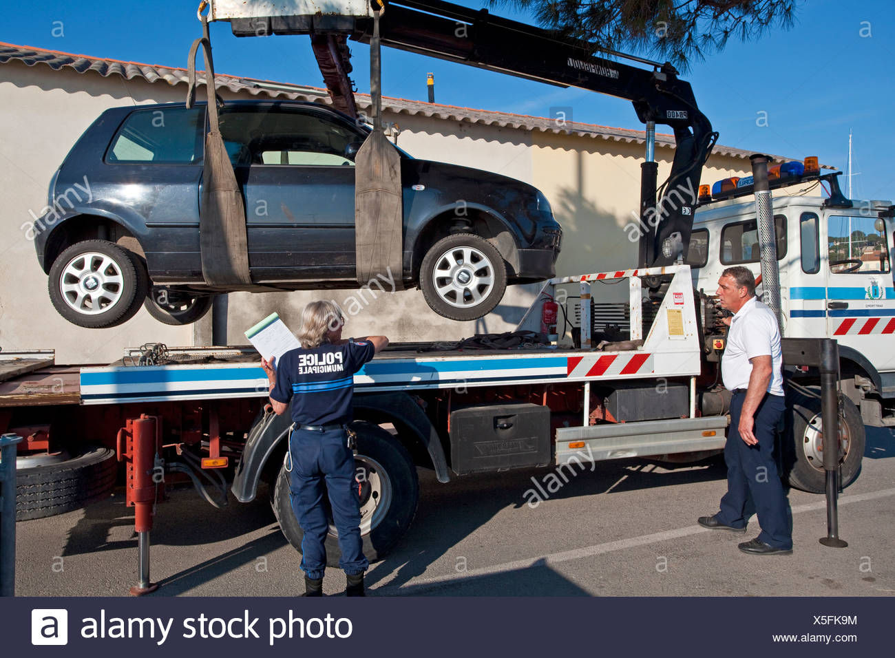An illegally parked car being towed away, the port of St Tropez, Var, Cote d'Azur, Southern France, France, Europe - Stock Image