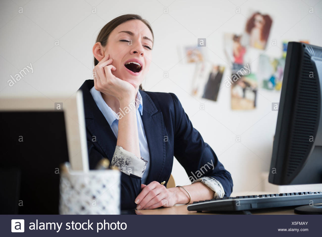 Woman yawning in office Stock Photo