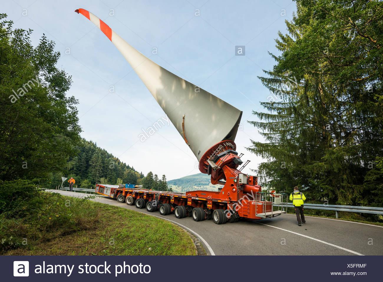 Heavy transport, wind turbine blade on heavy goods vehicle, curvy road in Schönau, Black Forest, Baden-Württemberg, Germany - Stock Image