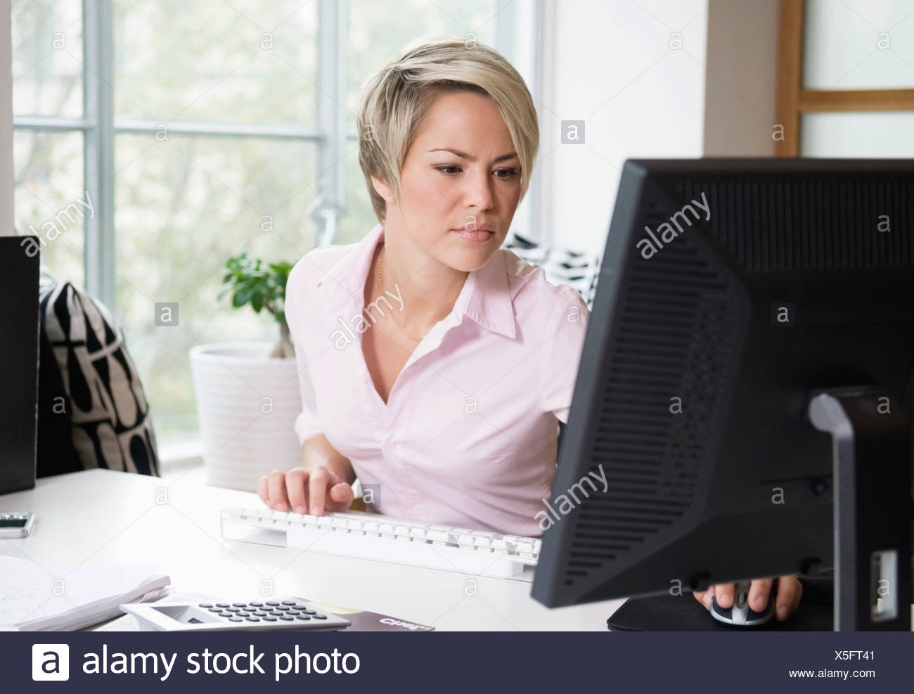 Young woman at work - Stock Image