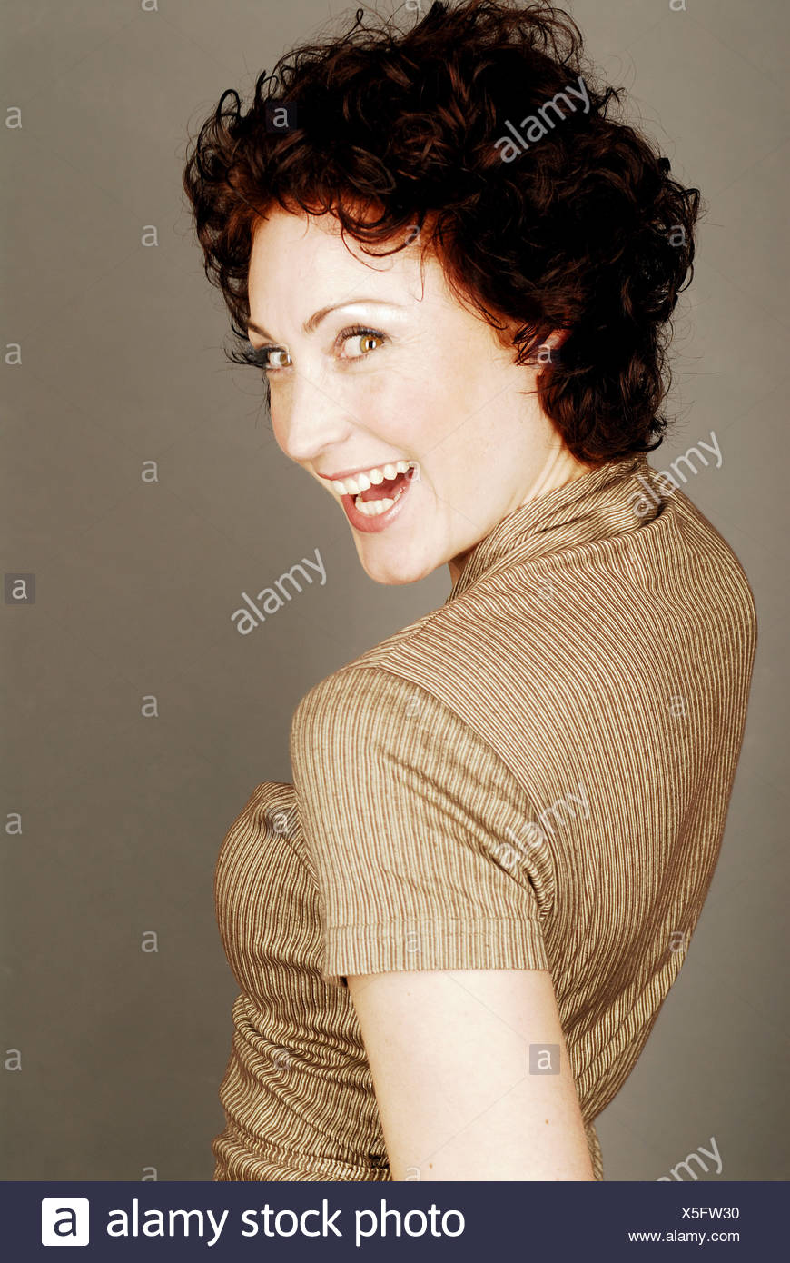 woman dark-haired laughing gaze shoulder portrait - Stock Image