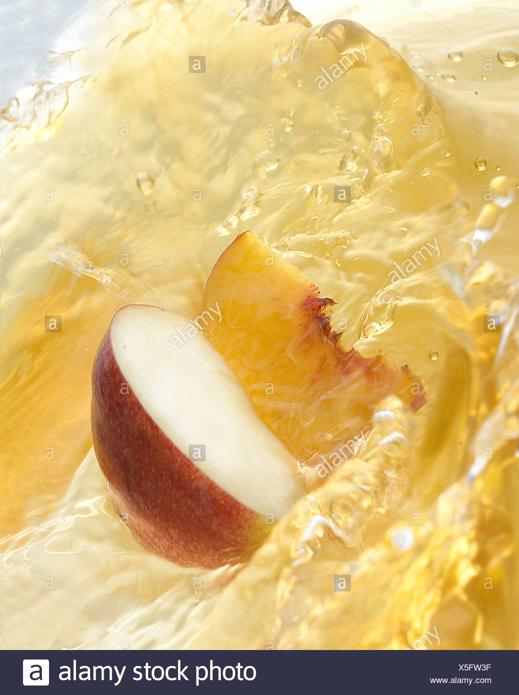 A slice of apple and a slice of peach in juice - Stock Image
