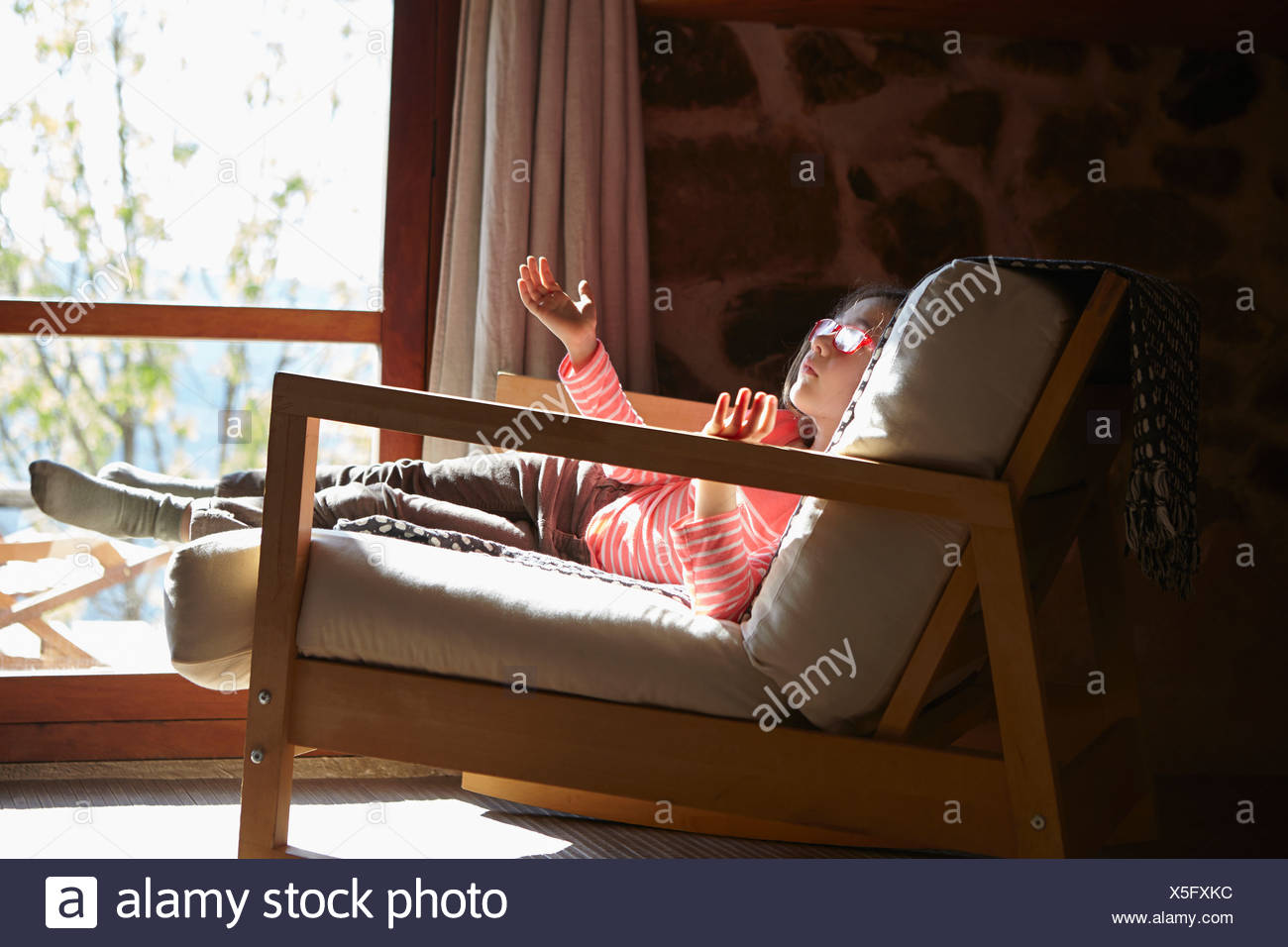 Young girl sitting on rocking chair daydreaming - Stock Image