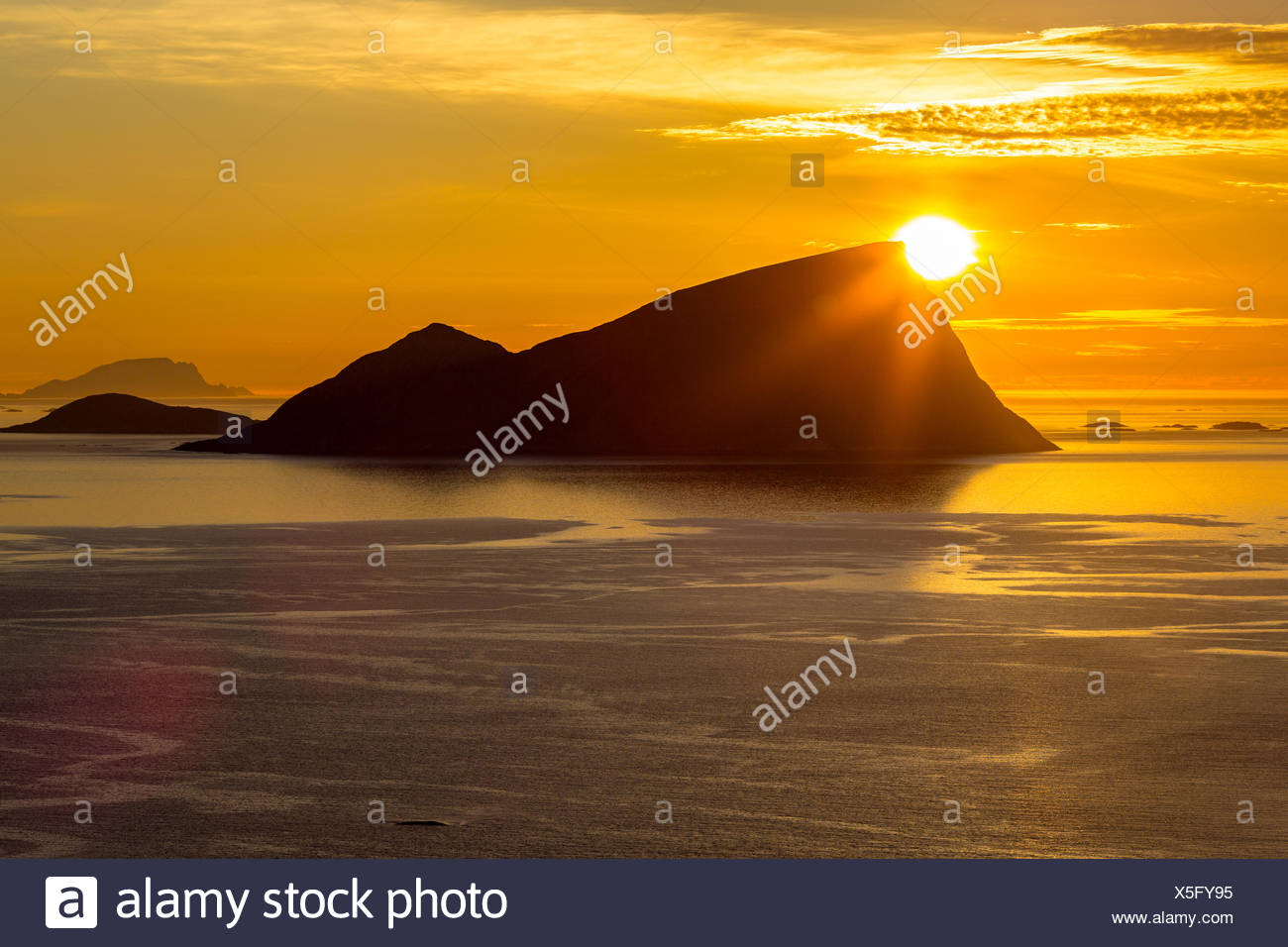 Silhouette Rock Formation At Beach Against Orange Sky - Stock Image