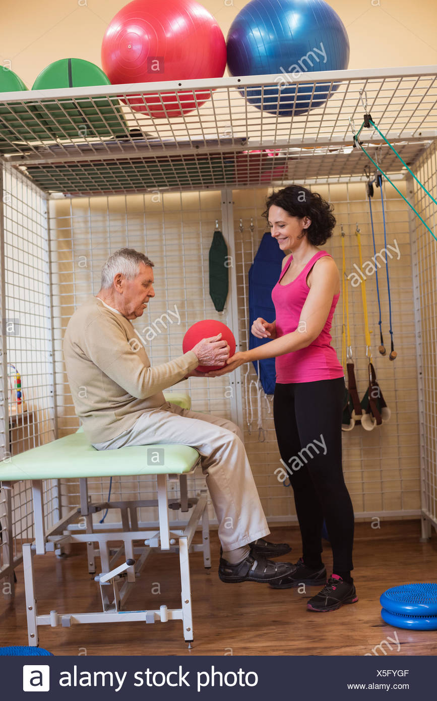 Female therapist assisting senior man with exercise ball - Stock Image