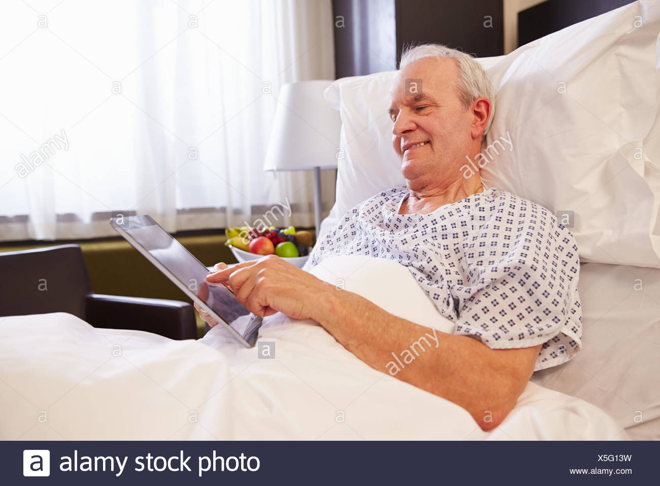 Senior Male Patient Using Digital Tablet In Hospital Bed - Stock Image