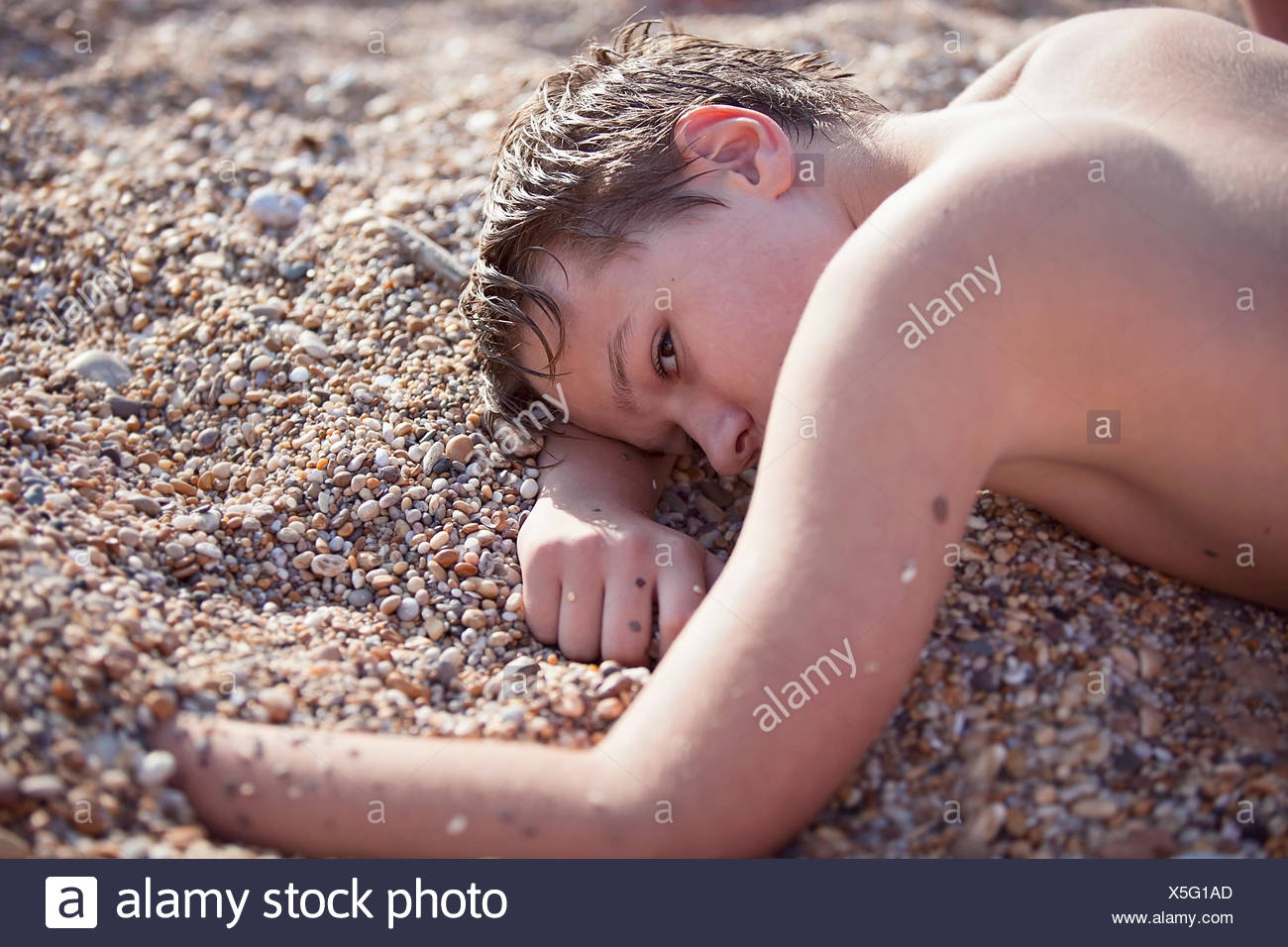 Young boy (12-13) laying on sandy beach - Stock Image