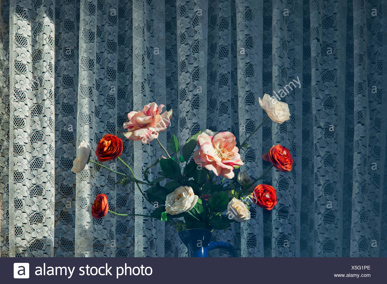 Artificial roses in front of a curtain, Bavaria, Germany - Stock Image