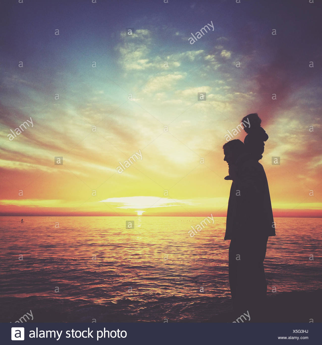 Silhouette of boy sitting on his father's shoulders, Laguna beach, California, America, USA Stock Photo