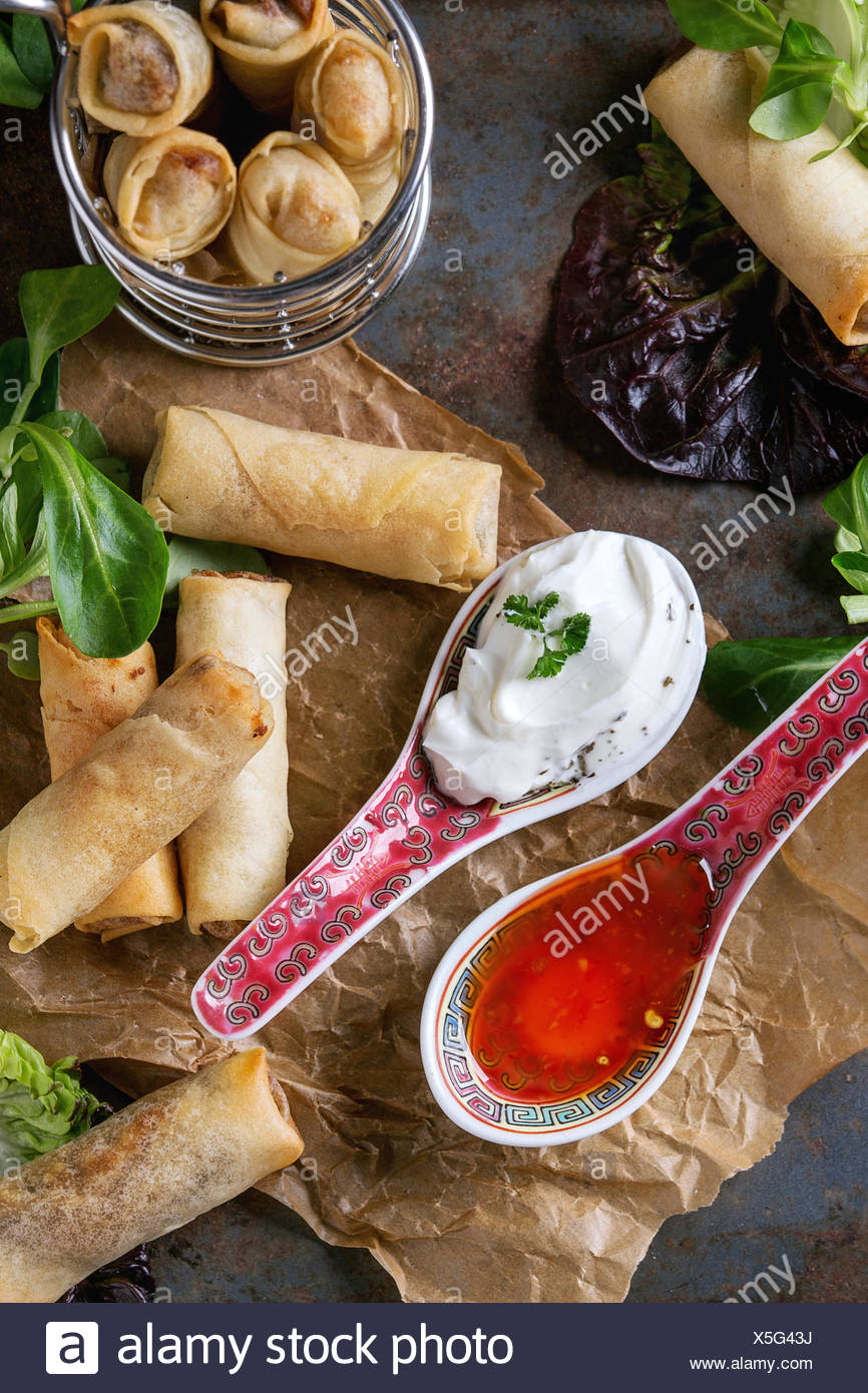 Fried spring rolls with red and white sauces in china spoons, served on crumpled paper and in fry basket with green salad and wooden chopsticks over o - Stock Image