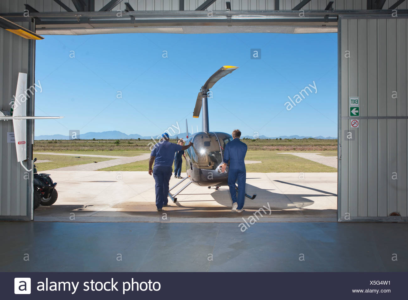 Pilots pushing helicopter onto tarmac - Stock Image