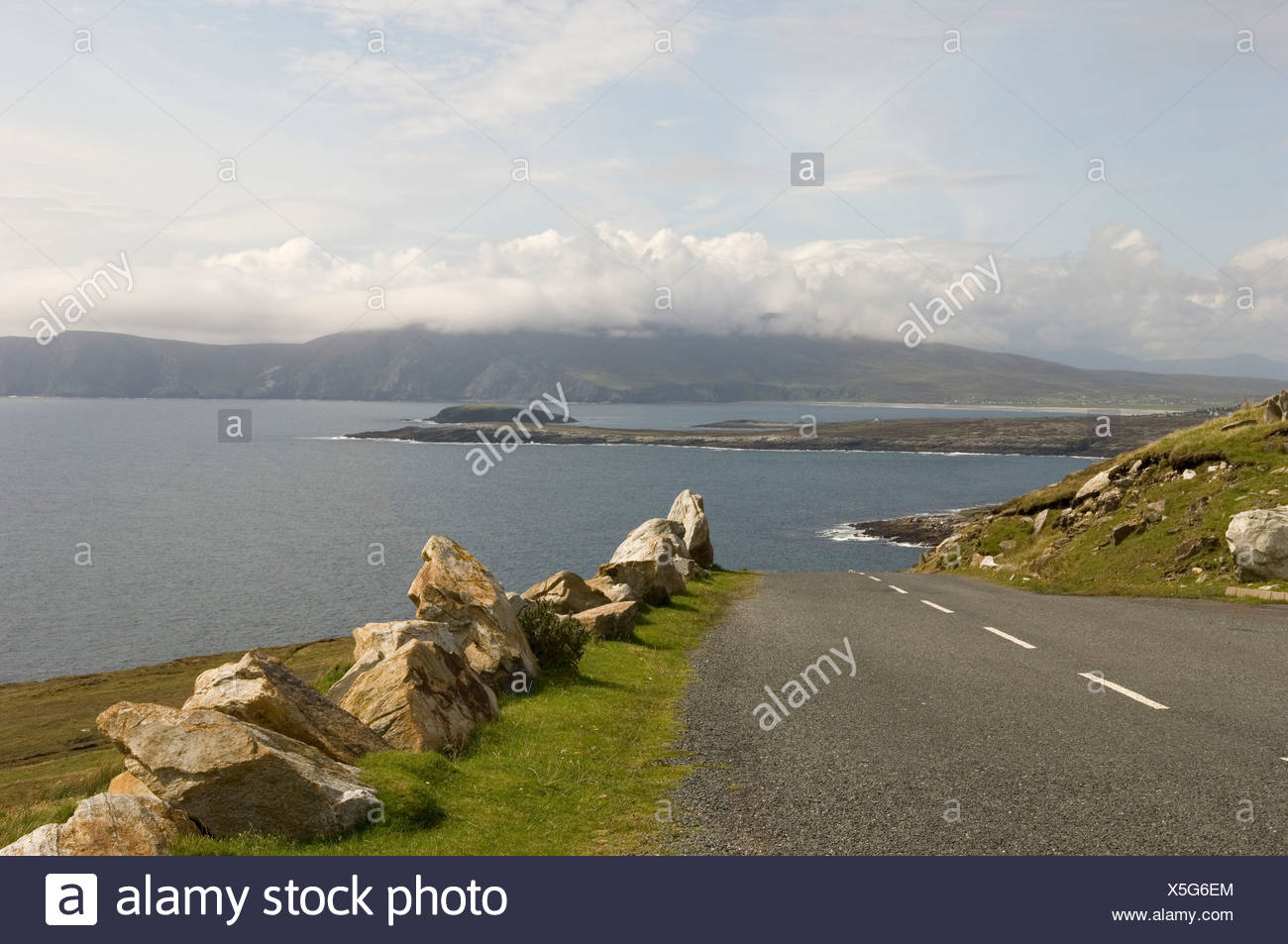 Republic of Ireland, County Mayo, Achill Island, road lined with rocks - Stock Image