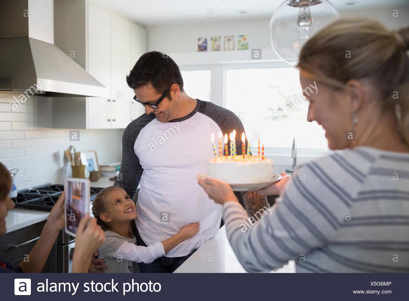 Family celebrating with birthday cake in kitchen - Stock Image
