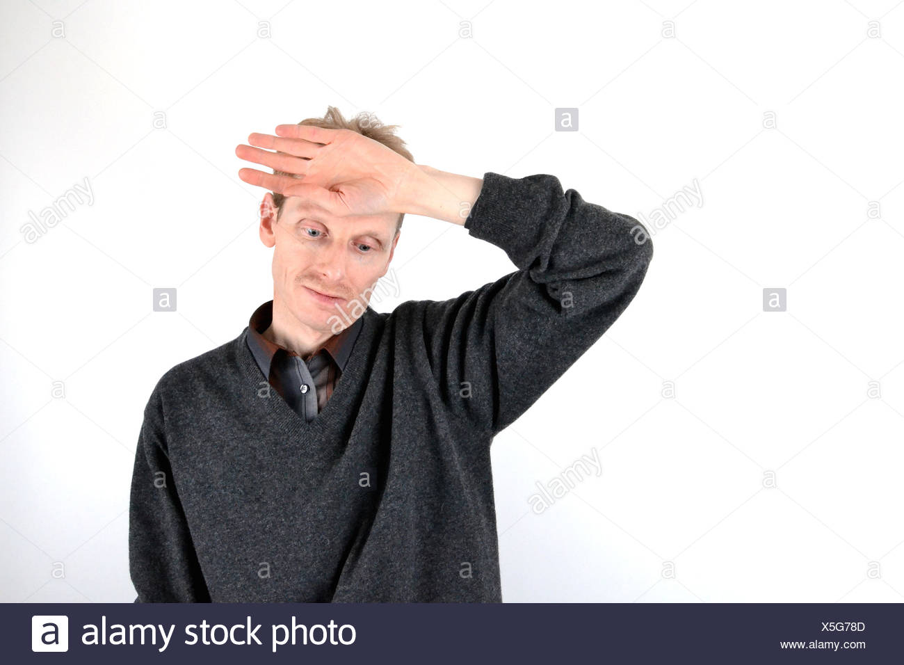 Blonde man who has his hand on his forehead Stock Photo