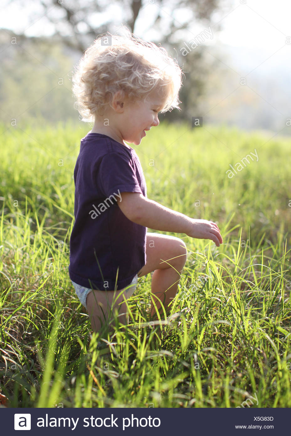 Boy kneeling in the grass - Stock Image