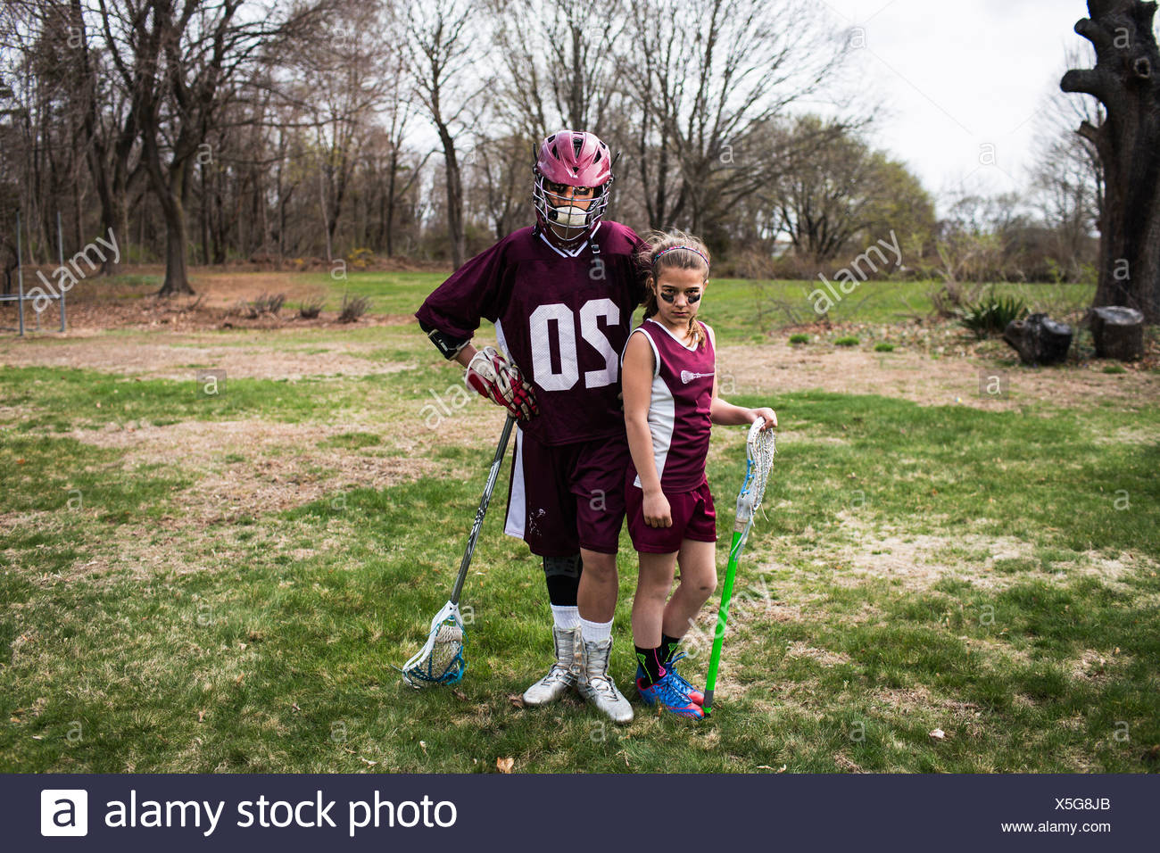 Brother and sister wearing lacrosse uniforms - Stock Image