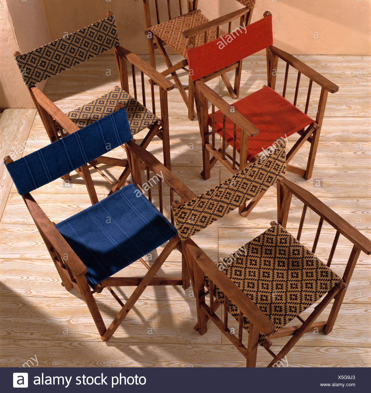 Close Up Of Group Of Red, Blue And Patterned Wooden Directoru0027s Chairs