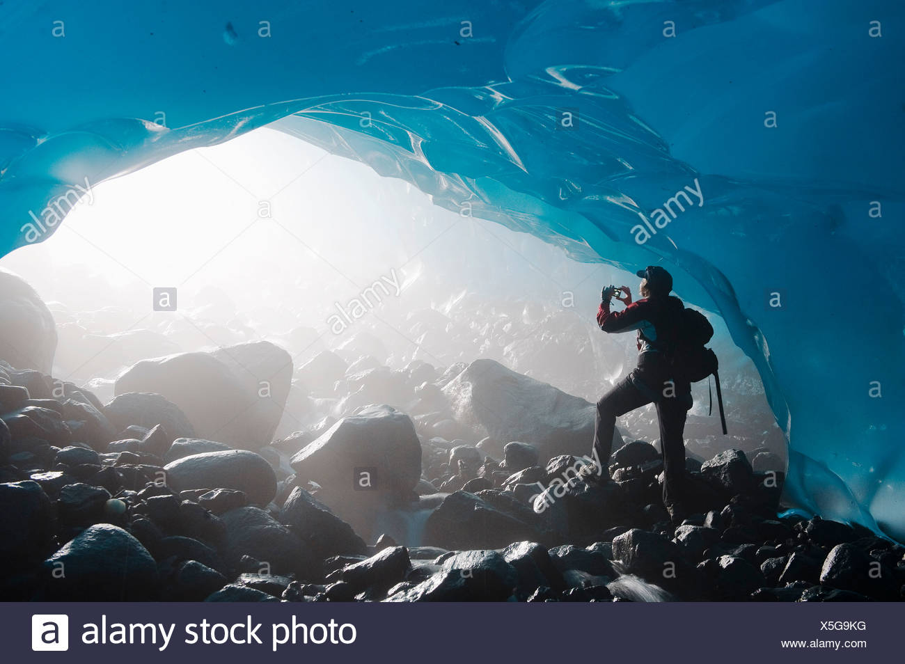 A hiker takes a photograph of the entrance of an ice cave from the inside of the Mendenhall Glacier, Southeast Alaska, Summer - Stock Image