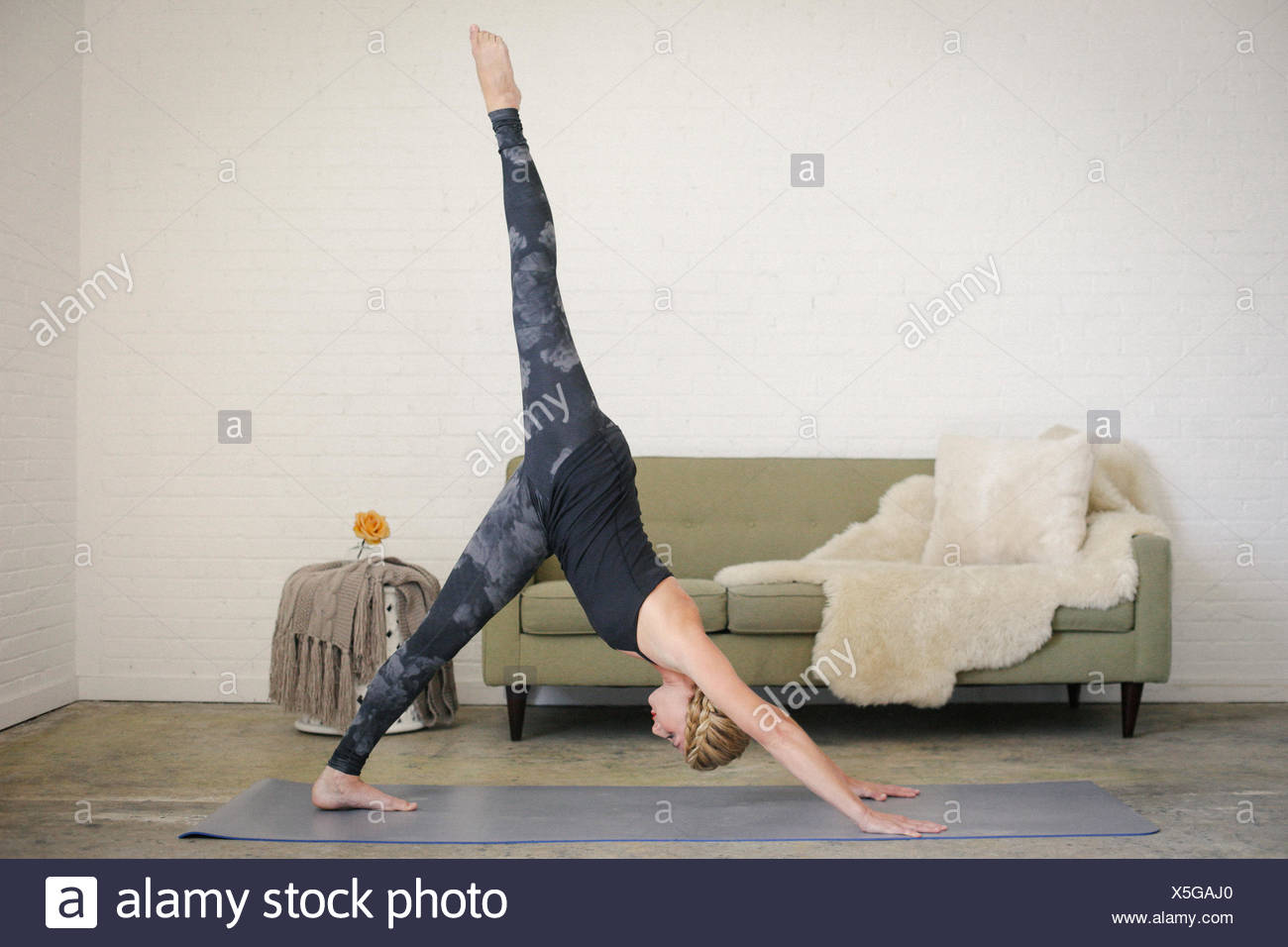 A blonde woman standing on a yoga mat in a room, bending down with her hands touching the floor, one leg raised. - Stock Image