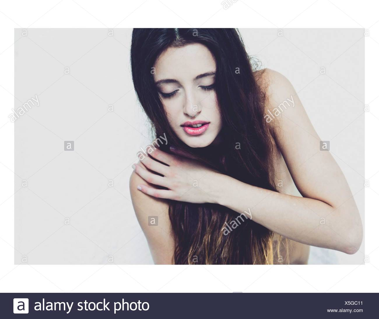 High Angle View Of Beautiful Young Woman With Arms Crossed Against White Background - Stock Image