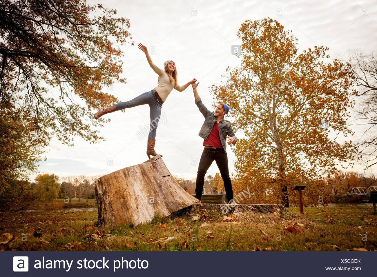 Young couple playing on tree stump in autumn park - Stock Image