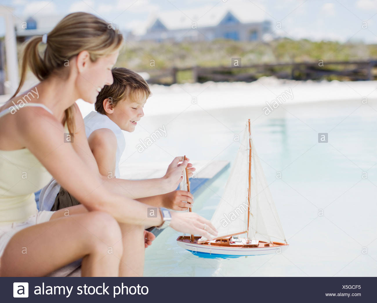 Mother and son playing with miniature boat in pool - Stock Image