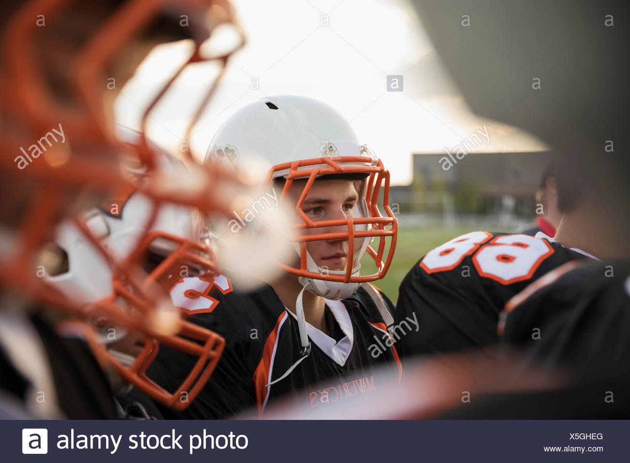 Teenage boy high school football player wearing helmet and sports uniform - Stock Image