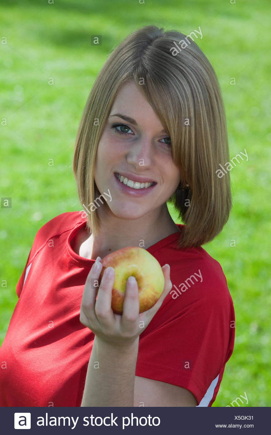 young blond-haired woman with apple, Germany - Stock Image