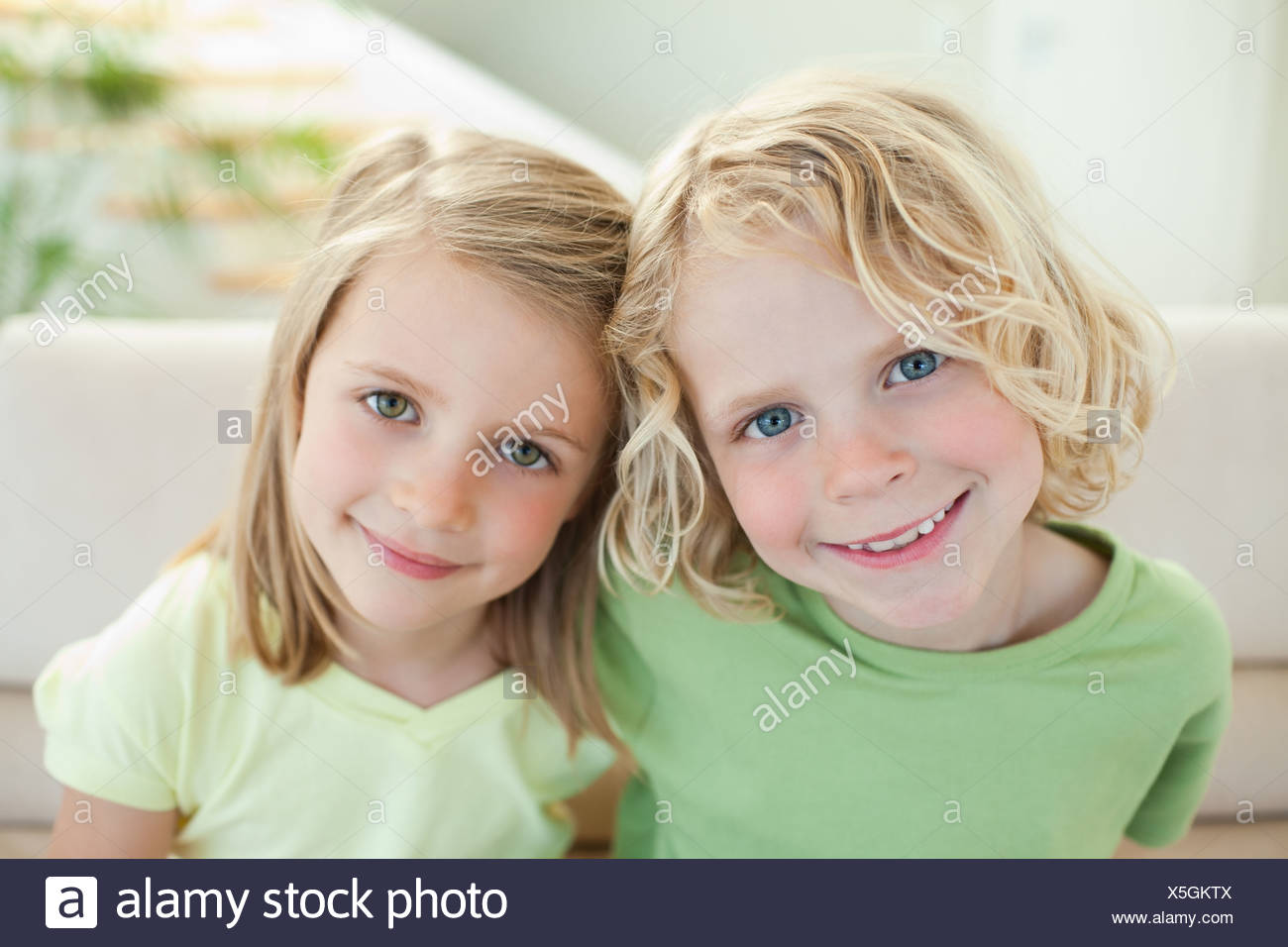 Smiling siblings on the sofa - Stock Image