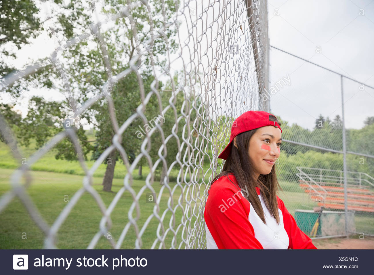 Baseball player standing by chain link fence - Stock Image