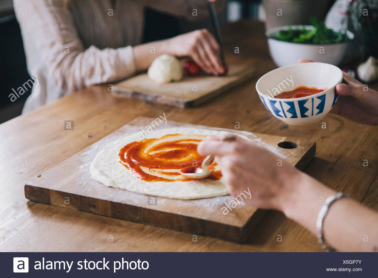 Cropped image of woman spreading tomato sauce over pizza dough - Stock Image