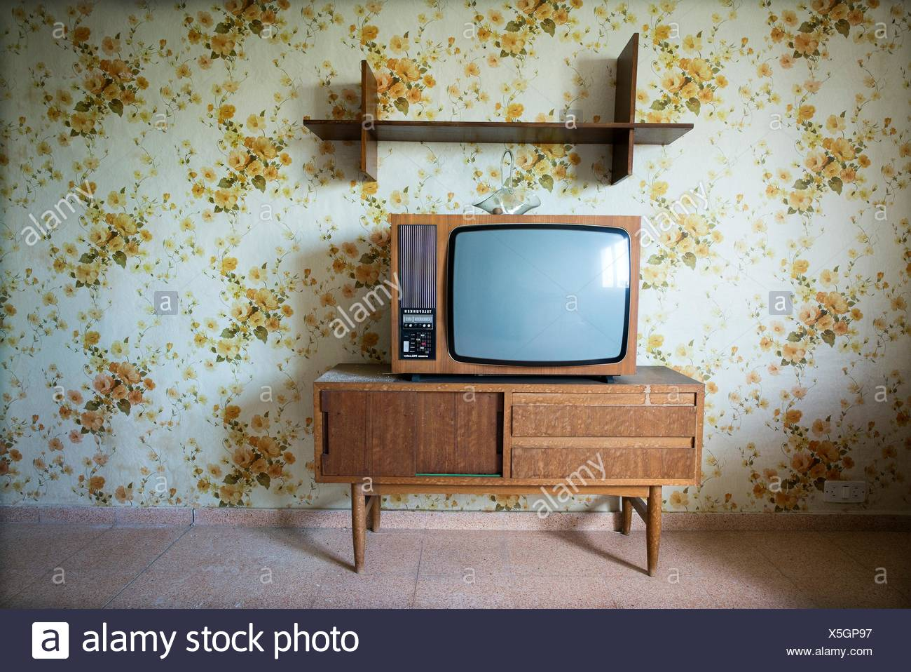 vintage living room with a floral wallpaper in the wall and ta vintage tv on top of a cabinet ma mahon menorca biosphere X5GP97