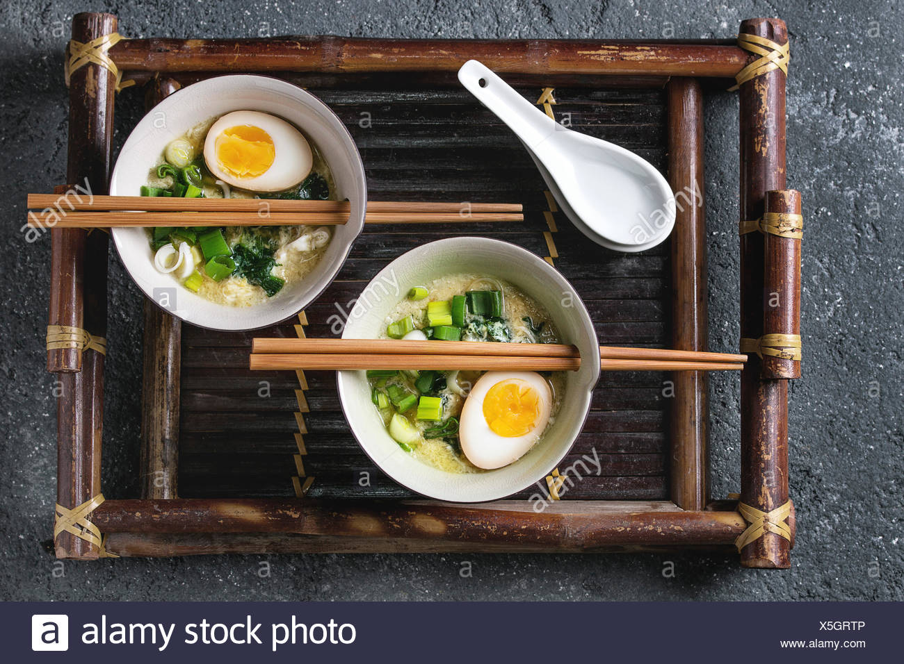 Two bowls with asian style soup with scrambled eggs, half of marinated egg, spring onion, spinach served with wood chopsticks and spoons on bamboo tra - Stock Image