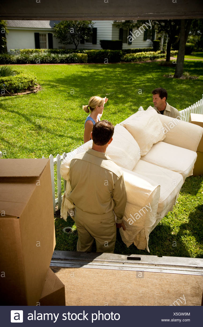 Woman directing removal men carrying sofa into new home - Stock Image