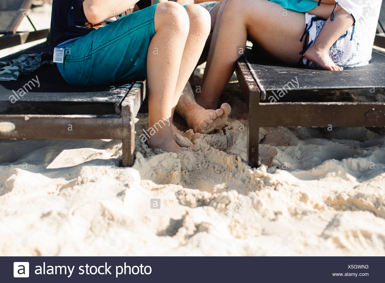 Mother and son sitting on sun loungers, mother holding young daughter, low section - Stock Image