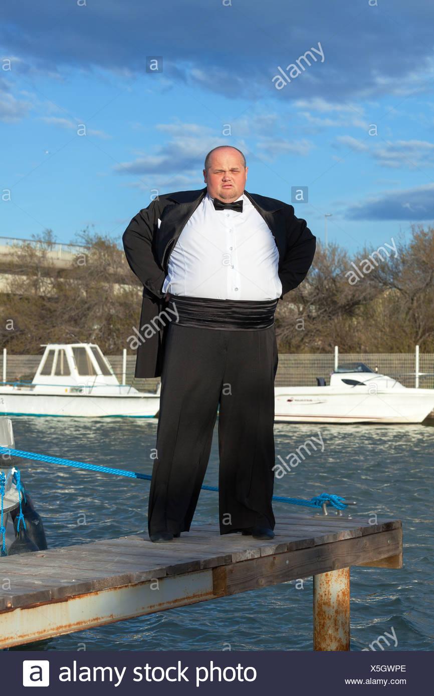 Fat man in tuxedo on pier - Stock Image
