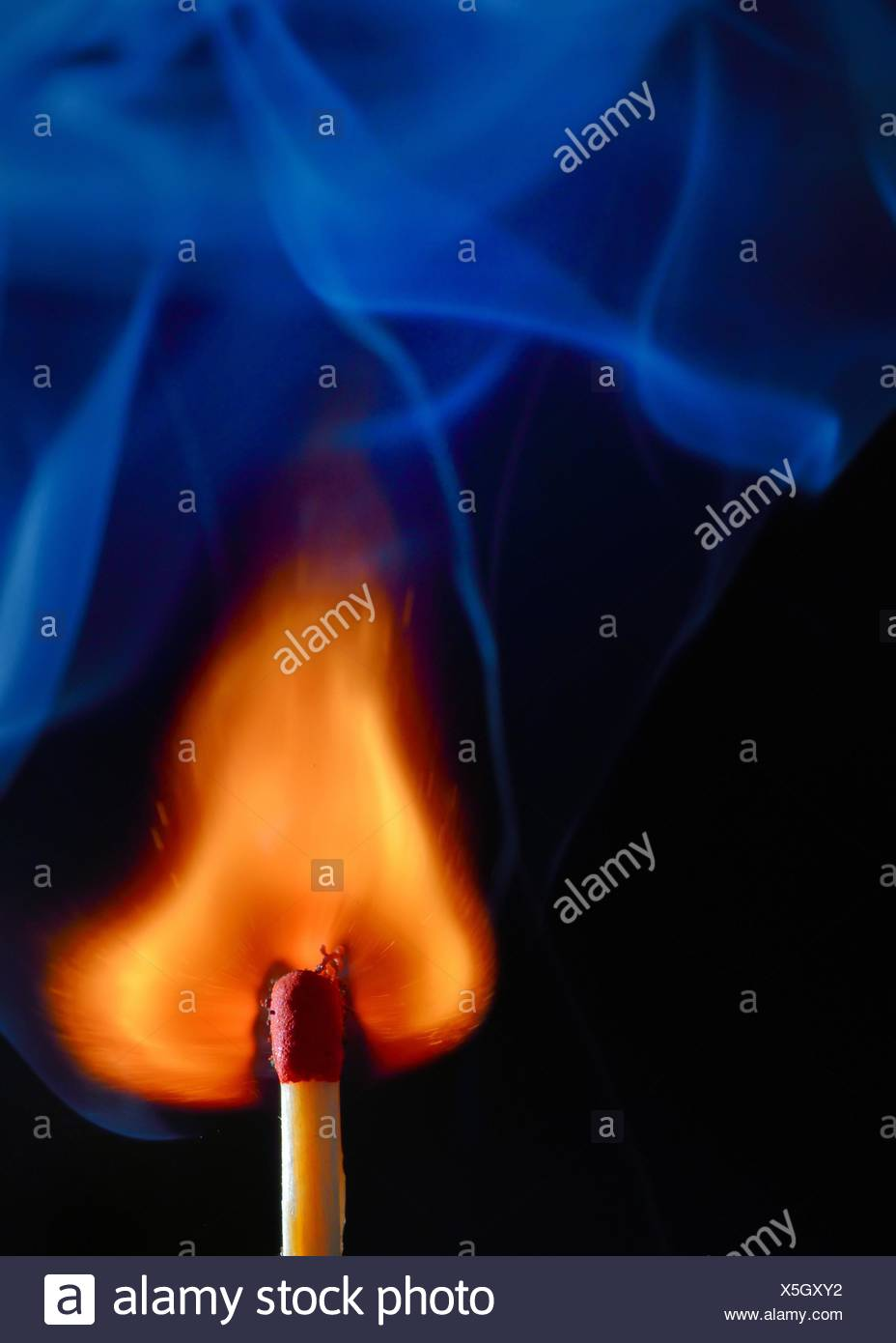 Burning match with blue smoke on black background. - Stock Image