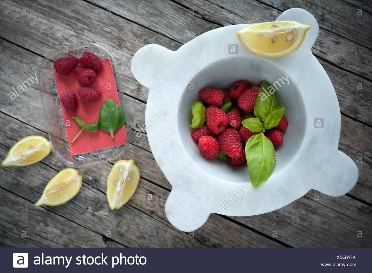 Mortar with fresh raspberries, basil leaves and lemon slices, above shot. - Stock Image