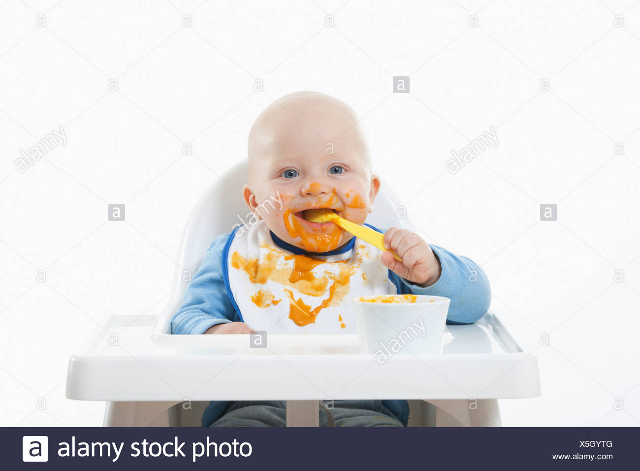 Baby boy (6- 11 Months) eating baby food with baby spoon Stock Photo