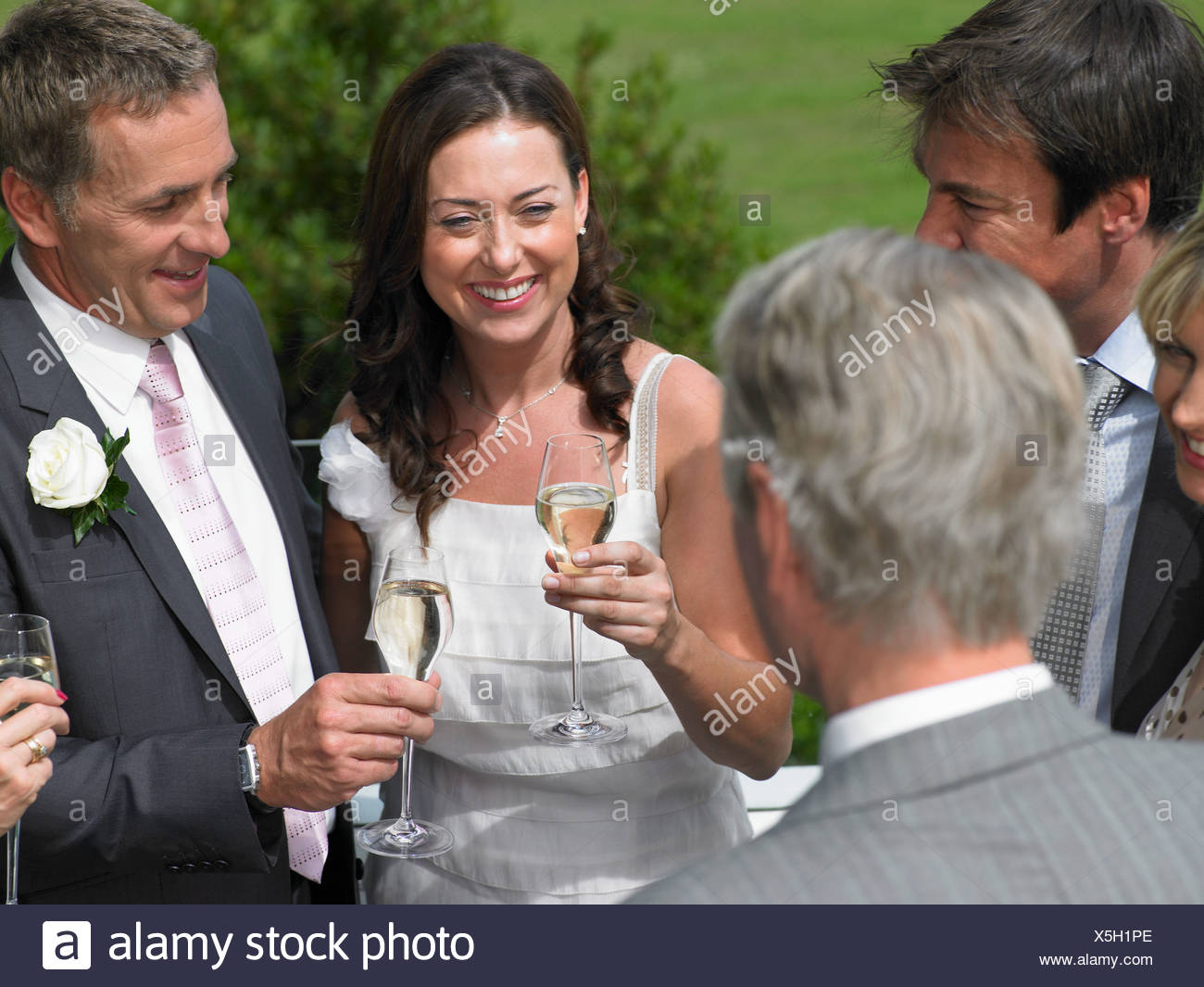 Bride and groom with wedding guests - Stock Image