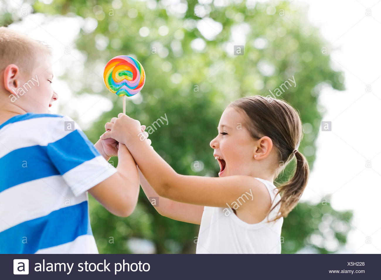Young boy (6-7) teasing sister (4-5) - Stock Image